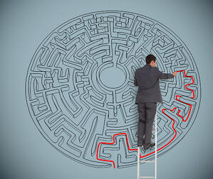 Businessman on ladder drawing red line to solve a maze on grey wall